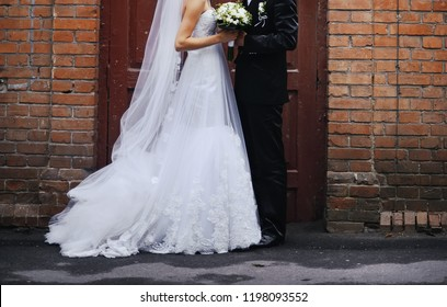 Bride and groom together. Wedding day atributes, suit, dress and bouquet