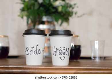 Bride and groom to-go disposable coffee cups at a wedding reception.