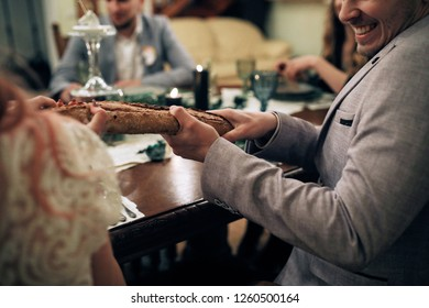 Bride and groom try to split french bread sitting at the dinner table