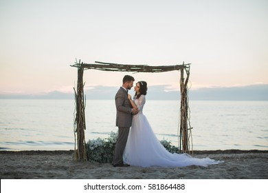 The bride and groom under archway on beach. Sunset, twilight.