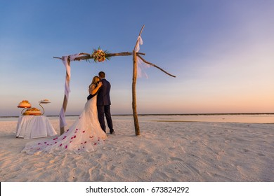The bride and groom under archway on beach. Romantic wedding background.
