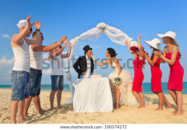 Bride and Groom Under Archway on Beach trying to take a bite of wedding cake.