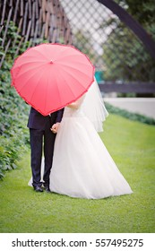 The bride and groom under a red umbrella in the form of heart