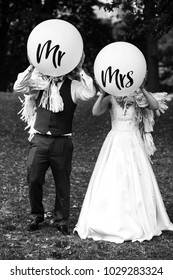 Bride and groom walk with balloons with lettering 'Mr' and 'Mrs' across the lawn in park