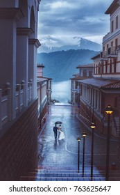 The bride and groom walk in the evening under an umbrella. Mountains, rain, fog.