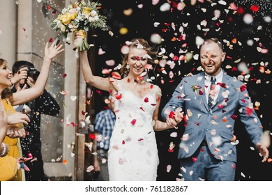 Bride and groom walk out of the church in the rain of petals and rice