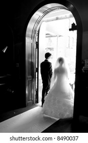 bride & groom walk toward the church door