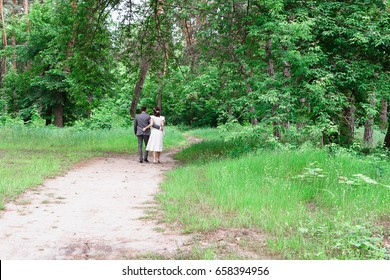 The bride and groom walk in the woods