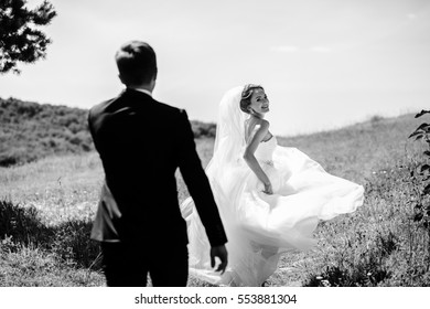 The bride and  groom walking along field