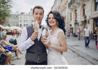 bride and groom walking along a sunny city and eating ice cream