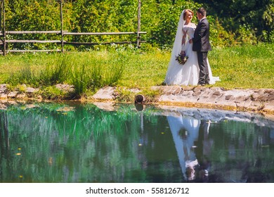Bride and groom walking near beautiful lake in forest .Wedding couple in love