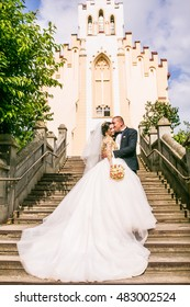 bride and groom walking near trees and church. Woman in yellow gold crown. Decorated yellow beads dress. Embracing couple. Looking each other. Adorable girl. Emotional picture.