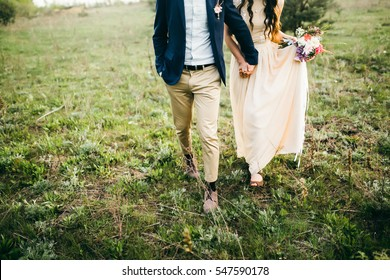 Bride and groom walking on the glade