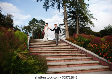 Bride and groom walking in park after wedding ceremony