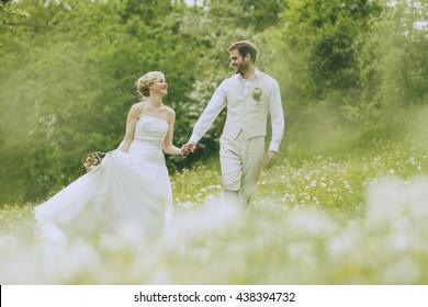 Bride and groom walking together holding hands on a gorgeous blooming summer meadow and laughing at each other.