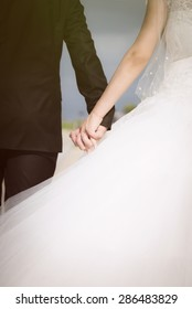 Bride and groom walking while holding hands