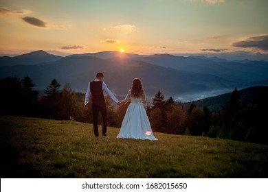 Bride and groom watch the sunset standing on the hill.