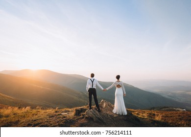 Bride and groom watch the sunset standing on the hill