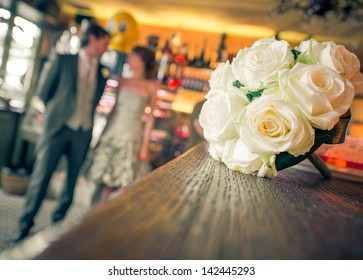 Bride, groom and wedding bouquet in a bar