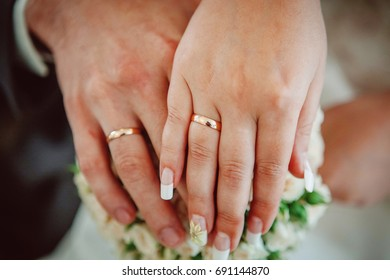 Bride and groom with wedding rings and bridal bouquet