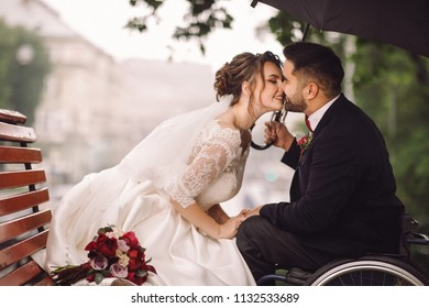 Bride and groom in the wheelchair sit kissing on the bench in the park