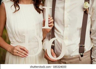 bride and groom with wooden words i do