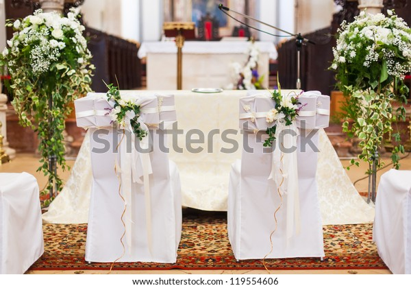 The bride and groom's chairs inside of the church.