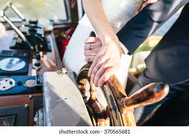 Bride and Grooms Hand and on a wooden Steering Wheel
