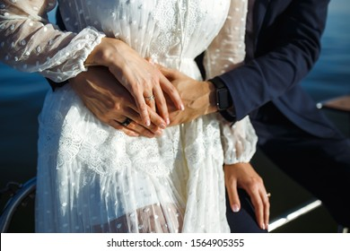 Bride and groom's hands with elegant wedding rings. Newlyweds hold hands with wedding ringson the background of sea and sun. Wedding details. Together. Wedding day.