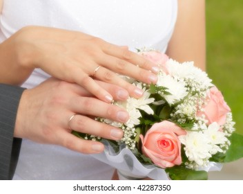 The bride and groom's hands together on the wedding bouquet
