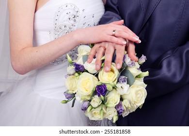 Bride and Groom's hands. Wedding bouquet.