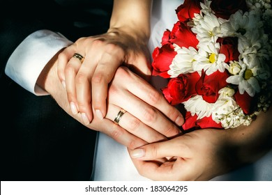 Bride and groom's hands with wedding rings, wedding bouquet.