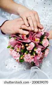 Bride and groom's hands with wedding rings near wedding bouquet