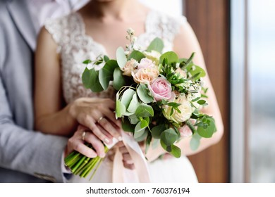 Bride and groom's hands with wedding rings. Newlywed couple holding stylish wedding bouquet