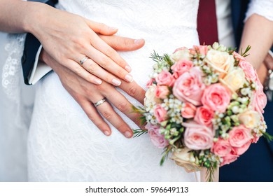 Bride hand with ring and wedding bouquet of flowers