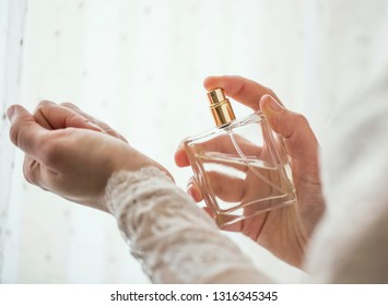 Bride hands applying perfume on her wrist, closeup selective focus