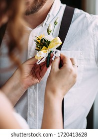 the bride helps the groom to attach a buttonhole.boutonniere consists of white and yellow flowers.the groom is happy.future wife attaches boutonniere to groom's suspenders.
