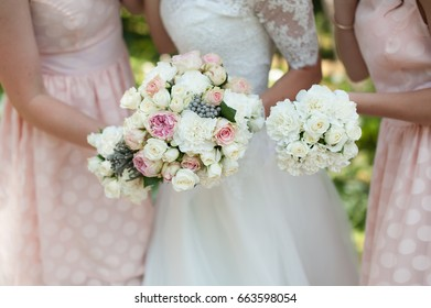 The bride and her bridesmaid in pink with flowers at the wedding, With bouquets in hand.