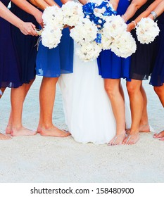 A bride and her bridesmaids holding flowers at beach in Key West Florida