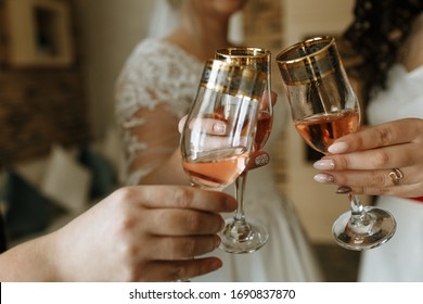 The bride and her friends at the wedding holds glasses with champagne.