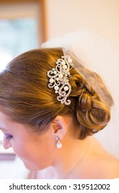 Bride with her hair up and a jewelry piece pinned in her updo.