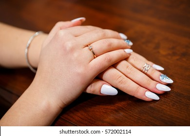 Bride with her hands folded neatly on a table with wedding ring