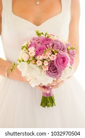 the bride in her hands holds a beautiful bouquet of purple roses and white hydrangeas