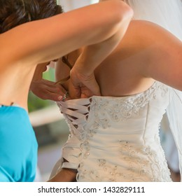 33296e9ce A bride and her maid of honor are trying to get the bride's corset style  dress