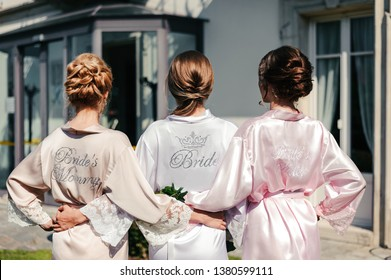 The bride and her mom and sister stand back. They are wearing silk robes with inscriptions on the back.