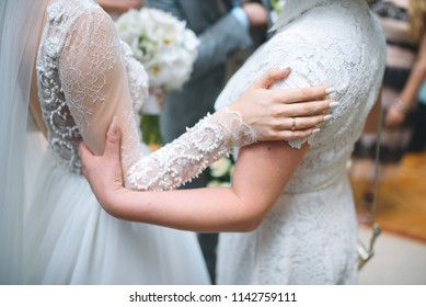 bride and her mother in white dresses holding hands