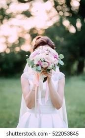 bride hiding behind a wedding bouquet of flowers