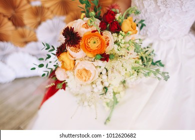 Bride is holding autumn wedding bouquet with red, orange and yellow flowers
