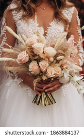 Bride holding boho bouquet against the background of trees with red leaves in autumn