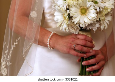 Bride holding a bouquet with both hands while displaying her engagement ring and pearl bracelet